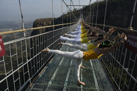 05 Nov 2015, Hunan Province, China --- Chinese women perform yoga on the 180-meter-high and 300 meter-long glass-bottomed suspension bridge at the Shiniuzhai National Geopark in Pingjiang county, in central China's Hunan province, 35 November 2015. More than 100 people performed yoga on a glass-bottomed suspension bridge that sits 180 meters above the ground at the Shiniuzhai National Geopark in Pingjiang county, in central China's Hunan province on Thursday (5 November 2015). The 300 meter-long suspended bridge, which apparently sways in the wind, spans a chasm at the national park, popular with tourists for its unique rock formations and geography. Walkers see clear, stomach-churning views of the ground 180 meters below. Park management authorities added a small section of glass last year but decided to transform the entire length of the crossing. The floor is made of a double layer of glass and is --- Image by © Imaginechina/Corbis